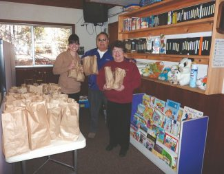 With the snack lunches for the needed are, from left, Emily Peart, Women's Center grant coordinator, Elk Roger Barragan and wife Jeanne.