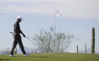 Tiger Woods walks along the fourth green before putting against Nick Watney during the Match Play Championship golf tournament, Thursday, Feb. 23, 2012, in Marana, Ariz.  (AP Photo/Julie Jacobson)