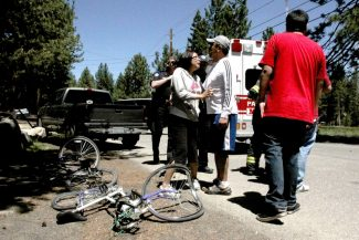 Adam Jensen / Tahoe Daily Tribune.Friends and family of a woman who was struck by a truck while riding her bicycle Monday speak with police and firefighters.