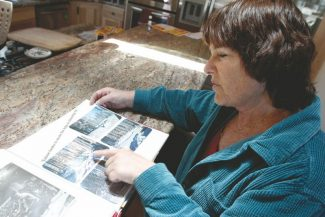 Adam Jensen / Tahoe Daily TribunePyramid Circle resident Nancy Muller looks through a scrapbook of news clippings and photos from the Angora fire Friday. Muller rebuilt her home after it was destroyed in the 2007 blaze, the fifth anniversary of which is Sunday.