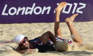 Todd Rogers US dives into sand during the Beach Volleyball match against Italy at the 2012 Summer Olympics, Friday, Aug. 3, 2012, in London. (AP Photo/Petr David Josek)