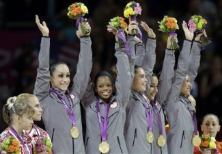 U.S. gymnasts, top left to right, Jordyn Wieber, Gabrielle Douglas, McKayla Maroney, Alexandra Raisman and Kyla Ross raise their hands and celebrate during the medal ceremony of the Artistic Gymnastics women's team final at the 2012 Summer Olympics, Tuesday, July 31, 2012, in London.  U.S. won the gold. (AP Photo/Julie Jacobson)