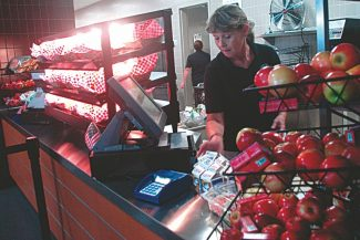 Axie Navas / Tahoe Daily TribuneSTHS cafeteria staff set out organic gala apples fresh from the farm and milk in preparation for the high school lunch period on Thursday.
