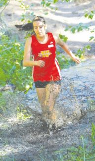 Courtesy of Boyd Dangtondee Senior Alexa Cooper splashes her way through a muddy section of trail in the 3.1 mile varsity run at the Warrior's home cross country meet on Sept. 7.