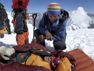 AP Photo/Garrett Madison, Alpine Ascents InternatiAn unidentified rescuer speaks to an unidentified survivor in the debris field of an avalanche on Mount Manaslu in northern Nepal on Sunday, Sept. 23. Rescue helicopters flew over the high slopes of the northern Nepal peak again Monday to search for climbers lost in an avalanche that killed at least nine mountaineers and injured others. Many of the climbers were French, German and Italian.
