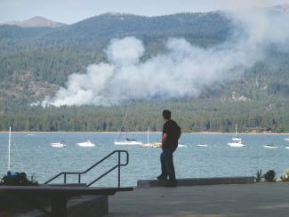 Adam Jensen / Tahoe Daily TribuneAn onlooker watches a Friday afternoon fire in Round Hill from Lakeview Commons.