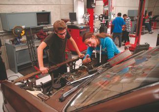Axie Navas / Tahoe Daily TribuneSouth Tahoe High School juniors Becca Wesson and Donovan Robins work on the engine of a Nissan truck Monday at the high school.