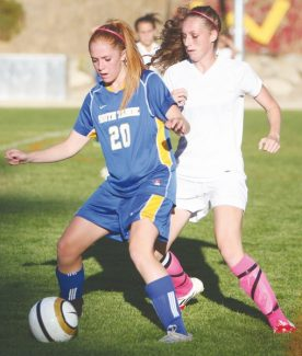 Becky Regan / Tahoe Daily Tribune South Tahoe's Brittney Hubberts and Whittell's Sierra Forvilly battle in midfield for the ball Monday. Separate Division III/IV regional and state tournaments were passed this week and the two schools will likely not meet on the soccer field again.