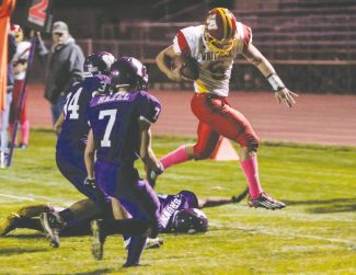 Courtesy of Boyd Dangtongdee Quarterback Austin Buyak leaps over Yerington in Whittell's away game Friday. The boys wore pink socks and shoelaces in honor of the Whittell athletic director, who is fighting breast cancer.