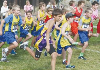 Becky Regan / Tahoe Daily Tribune. South Tahoe middle school runners charge off the starting line with Whittell runners, in the background sporting pink for breast cancer awareness month, during the sixth and seventh grade race Friday at Kahle Community Park.