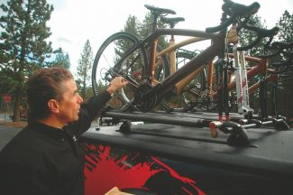 Axie Navas / Tahoe Daily TribuneIndependent distributor for Renovo Hardwood Bicycles Stephen Vorndran points to four of the hardwood bikes mounted on his truck. Vorndran, based out of Fair Oaks, Calif., travels throughout the region to sell the bicycles that are made almost entirely out of wood.