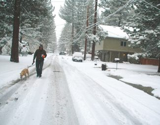 Axie NavasDave Dickinson and his dog Lucy walk down a snowy Modesto Avenue on Tuesday morning.