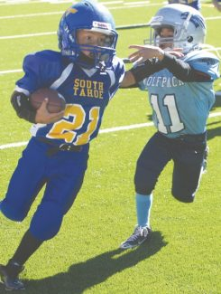 Becky Regan / Tahoe Daily Tribune Tiny Mite running back Joel Gomez Jr. charges downfield throwing a straight arm against a Reno defender Saturday at South Tahoe High School.