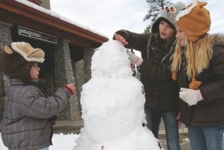 Adam Jensen / Tahoe Daily TribuneValley Springs residents Kyson Reese, 3, left, Lexi Reese, 8, middle, and Kendri Reese, 6, put the finishing touches on a snowman at Heavenly Village Tuesday afternoon.