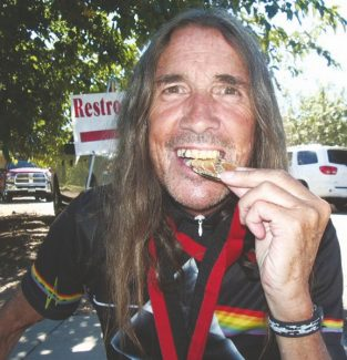 Courtesy of Joey LeavesleyJoey Leavesley checks the quality of the gold medal he picked up for his overall biking performance at the Senior World Games in St. George, Utah. Leavesley picked up three medals in the 65-69 age bracket.