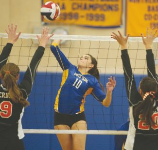 Becky Regan / Tahoe Daily Tribune Senior Emily Gardner rises above Fernley to sneak the ball through during South Tahoe's semifinal win at home Saturday. Gardner recorded nine kills and two blocks during the Northern 1-A Regional Championships.