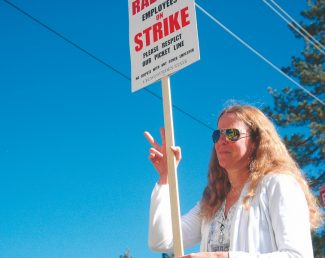 Axie Navas / Tahoe Daily TribuneTheresa Davis, one of the Raley's employees on strike, holds up the peace sign on Monday as a Raley's truck pulls out of the parking lot at the store near Stateline.