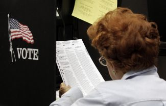 A voter reads her ballot as she prepares to cast her vote during the last day of early voting in Miami, Saturday, Nov. 3, 2012. Despite record turnout in many parts of the state, Florida Gov. Rick Scott rejected calls to extend early voting through Sunday to help alleviate long lines at the polls. (AP Photo/Alan Diaz)