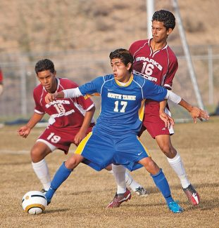 Matt Unrau/Elko Daily Free Press Jesus Martinez fends off a pair of Sparks defenders Friday in the Northern