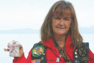 Adam Jensen / Tahoe Daily TribunePatty Smith, the mother of Sgt. Timothy Smith, shows a picture of her son at Lakeview Commons Friday morning. Discussions are taking place to name the nameless peak in the background to Patty Smith's right in honor of the Lake Tahoe Basin's fallen soldiers.