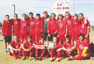 Courtesy of David Heldt-Werle The Warriors soccer team and head coach Royal Good surround the Division III state runner-up plaque after finals against Incline on Saturday in Henderson, Nev. The boys pushed the final match into overtime.
