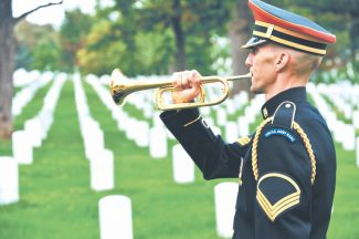 """Staff Sgt. Chris Branagan/Special to The TribuneJesse Tubb plays """"Taps"""" at Arlington National Cemetery."""