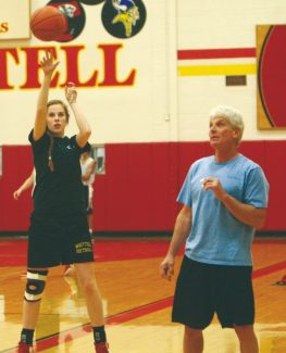 Becky Regan / Tahoe Daily Tribune Emily Harris follows her shot during practice while head coach Tom Esposito looks on at Whittell High School on Wednesday.