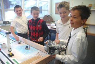 Axie Navas / Tahoe Daily TribuneJustin Smith, far left, Griffin Howell, Noah Lyle and Nate Toutolmin worked on their robot Tuesday at the Saint Theresa School. The boys are members of the school's FIRST LEGO League.