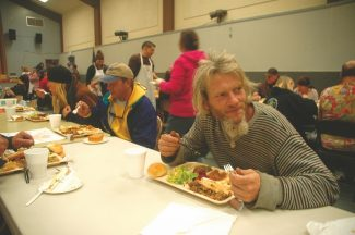 Axie Navas / Tahoe Daily TribuneAlex Magowan enjoys the turkey, gravy and stuffing served Monday in Grace Hall for Bread & Broth's Thanksgiving meal.