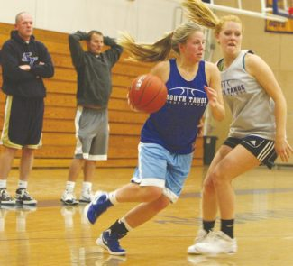 Becky Regan / Tahoe Daily Tribune  Bailey David drives past teammate Riley Chapman as she takes it to the hoop while the coaches look on in practice Nov. 26 at South Tahoe High School.