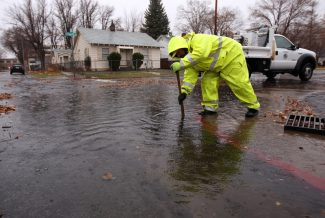 Eric Engles, with Carson City Public Works, clears a storm drain in Carson City, Nev, as a heavy, wet storm hits the Northern Nevada region on Sunday, Dec. 2, 2012. (AP Photo/Cathleen Allison)