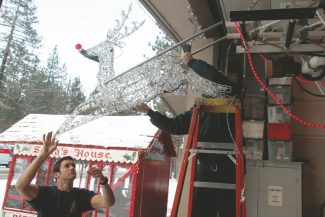 Adam Jensen / Tahoe Daily TribuneSouth Lake Tahoe reserve firefighter Chris Leisey, left, helps Captain Kenin Fairley attach Rudolph to the front of the department's holiday engine Tuesday afternoon.
