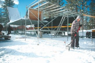 Axie Navas / Tahoe Daily Tribune A Snow Globe worker helps construct the big air setup Thursday. Local skiers and riders will be launching from the 30-foot scaffolding throughout the three-day music festival.