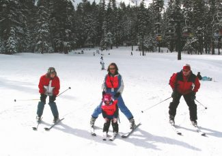 A Discovery Blind Sports guide leads a young blind skier down the mountain as her family tags along.