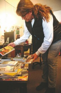 Axie Navas / Tahoe Daily TribuneKim Wyatt browses a selection of books displayed on a coffee table in the Meyers Bona Fide Books office.