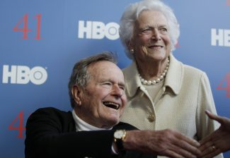 """FILE - In a Tuesday, June 12, 2012 file photo, former President George H.W. Bush, and his wife, former first lady Barbara Bush, arrive for the premiere of HBO's new documentary on his life near the family compound in Kennebunkport, Maine. Bush spokesman Jim McGrath said Wednesday, Dec. 26. 2012 that doctors at the Houston hospital where Bush has been treated for a month remain """"cautiously optimistic"""" that he will recover. Still, no discharge date has been set, and McGrath says that doctors are being cautious because at Bush's age """"sometimes issues crop up that are beyond anybody's ability to discern or foretell.""""(AP Photo/Charles Krupa, File)"""