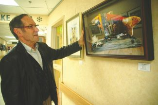 Axie Navas / Tahoe Daily TribuneEgon Klementi looks at a photograph of a salmon sculpture he made in the Snowflake Galley at Baron Memorial Hospital Wednesday.