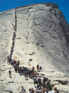 FILE - In this 2006 file photo provided by the National Park Service, tourists climb Half Dome at Yosemite National Park, Calif. A long-awaited plan that officials say will make safer the iconic climb up Half Dome in Yosemite National Park has been approved. The hand-rail cables that some environmental groups argued don't belong in a wilderness will stay, as will a lottery that will limit the number of hikers to roughly 400 a day. Over the past decade the route has been inundated with up to 1,200 nature lovers, causing traffic jams and a surge in calls for rescue.  (AP Photo/National Park Service, File)