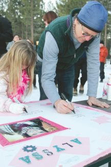 Adam Jensen / Tahoe Daily TribuneSouth Shore residents Amber Burdick, left, and John Friedrich sign a memorial poster for Alyssa Byrne at a vigil at Lakeview Commons Thursday evening.