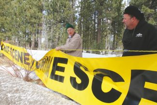 Adam Jensen / Tahoe Daily TribuneReno resident Mike Weston, left, and South Lake Tahoe resident Ty Robben string up oversized crime scene tape during a police protest along Al Tahoe Boulevard Monday afternoon.