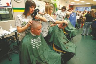 Tahoe Daily Tribune file Scott Smith of the South Lake Tahoe Fire Department gets his head shaved by Jill Wathers of Aqua Hair Design at the St. Baldrick's event, held at the South Tahoe Ice Arena last year.