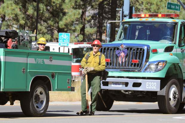 Area wildfire firefighters pause for a moment during Saturday's 50th anniversary parade.
