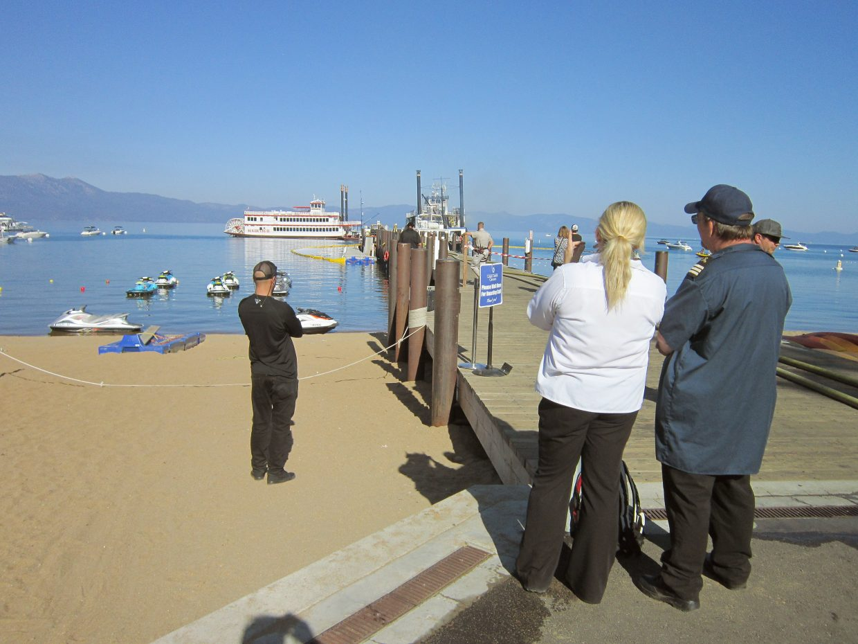 A crowd gathered Tuesday morning, Aug. 16, to watch firefighters extinguished flames on the historic Tahoe Queen.