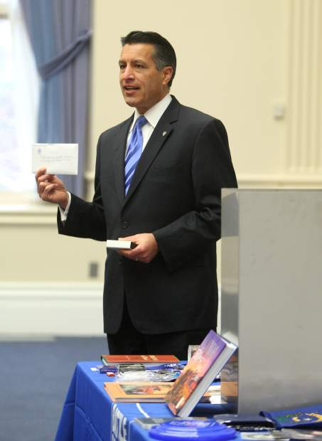 Gov. Brian Sandoval displays his hand-written letter to Nevada's future governor, that was placed into a time capsule on Monday.