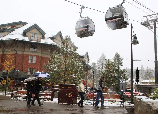 Area visitors pass under the Gondolas at South Lake Tahoe's Heavenly Village during the winter storm Monday, Nov. 2. Snow from the season's first storm blanketed the Tahoe Basin with significant snow totals at all elevations. Forecasters said the storm was not El Niño related but remain cautiously optimistic.