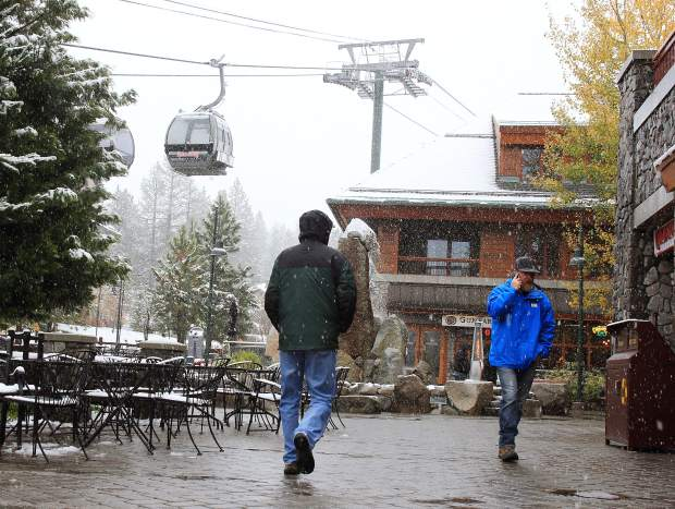 People walk through falling snow at Heavenly Village in South Lake Tahoe, California, Monday, Nov. 2. Weather forecasters said the early winter storm was a welcome sign but not EL Niño related.