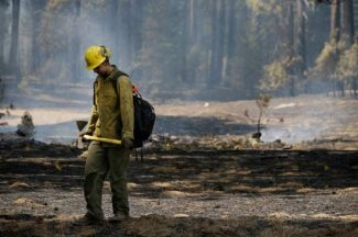 Firefighter Troy Drouin takes a short break before mopping up hot spots near Yosemite National Park, Calif., on Wednesday.