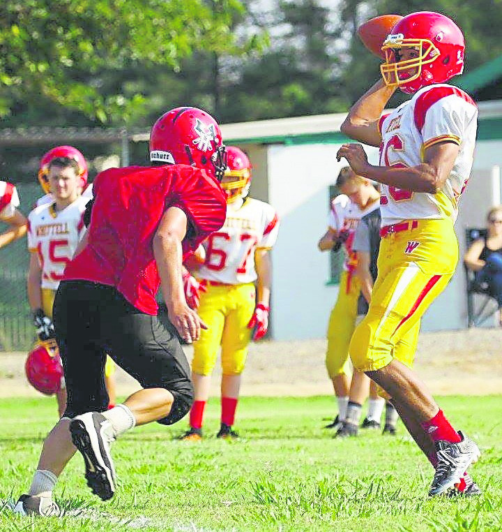 Warriors senior Dismas Womack fires a pass with a Hayfork rusher applying pressure Saturday.