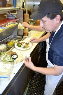 """Artemis kitchen manager Nelson Sagastume prepares a meal Friday. The business will be one of many restaurants serving food at """"An Evening of Food & Wine Tasting."""""""
