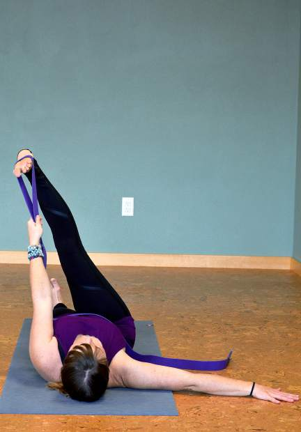 Reclining hand-to-big toe pose with strap, demonstrated by pro snowboarder Leslie Glenn.